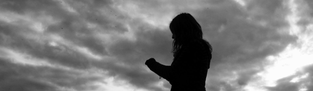 Silhouette of woman amid storm clouds