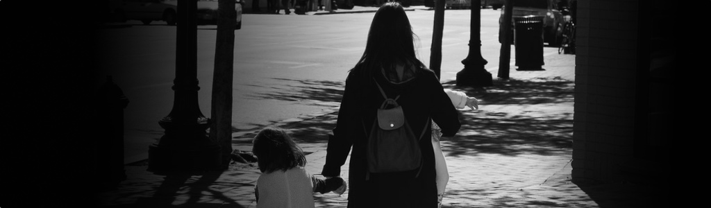 Mother and daughter holding hands on the street